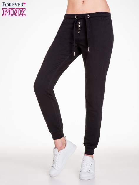 Czarne spodnie dresowe damskie z guziczkami                                  zdj.                                  1