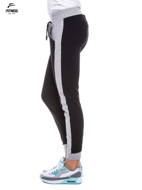 Czarne spodnie dresowe damskie z kontrastowymi lampasami po bokach                                  zdj.                                  6