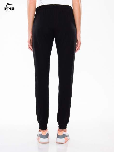 Czarne spodnie dresowe typu baggy z guzikami                                  zdj.                                  4