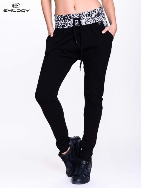 Czarne spodnie dresowe z białym pasem w panterkę