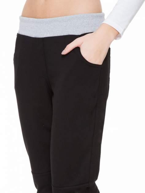 Czarne spodnie dresowe z guziczkami na nogawkach                                  zdj.                                  7