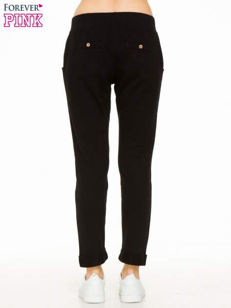 Czarne spodnie dresowe z guzikami wiązane w pasie                                  zdj.                                  3