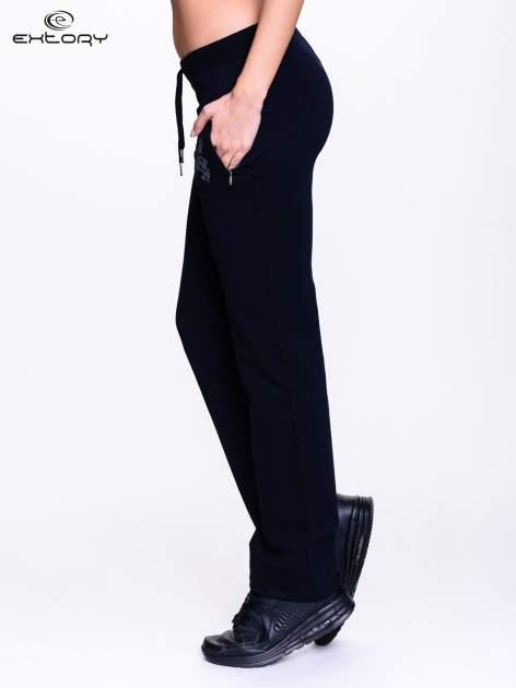 Czarne spodnie dresowe z kwiatem z dżetami i przeszyciem                                  zdj.                                  3