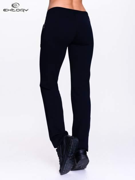 Czarne spodnie dresowe z kwiatem z dżetami i przeszyciem                                  zdj.                                  2