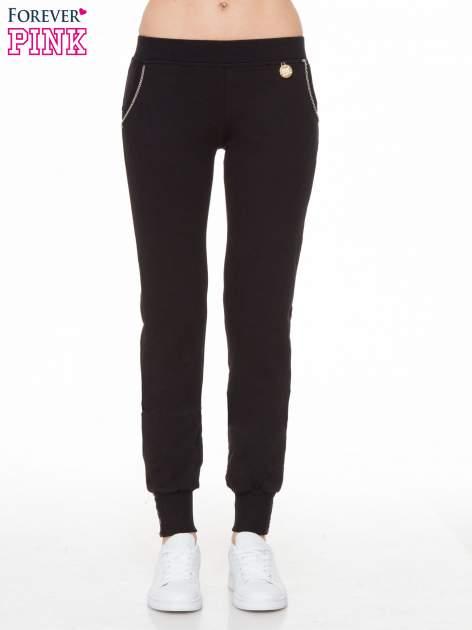 Czarne spodnie dresowe z łańcuszkami przy kieszeniach