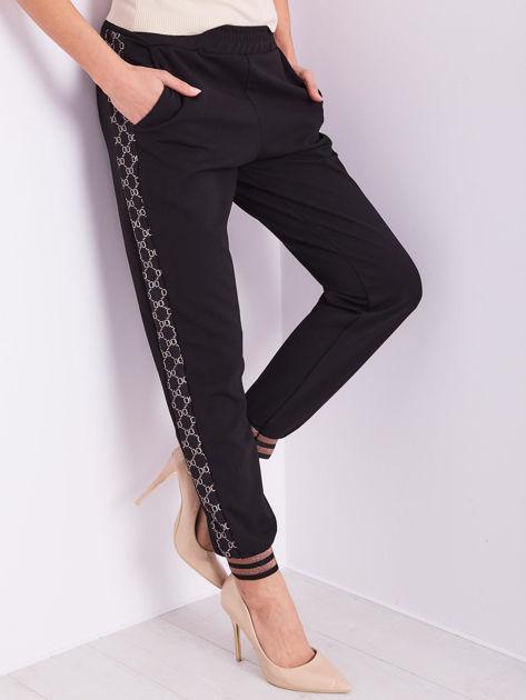 Czarne spodnie dresowe z ozdobnymi lampasami                              zdj.                              7