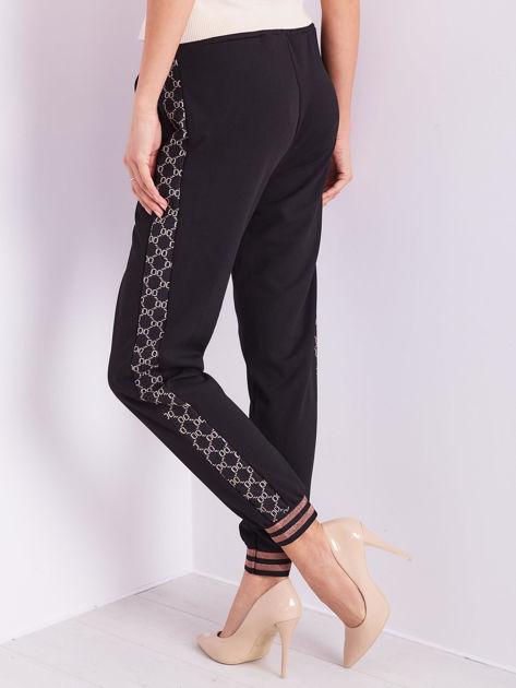 Czarne spodnie dresowe z ozdobnymi lampasami                              zdj.                              2