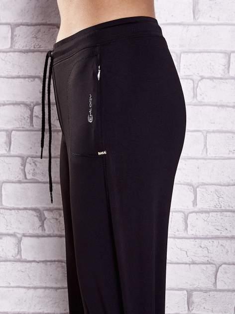 Czarne spodnie dresowe z wszytą kieszonką i troczkami                              zdj.                              5