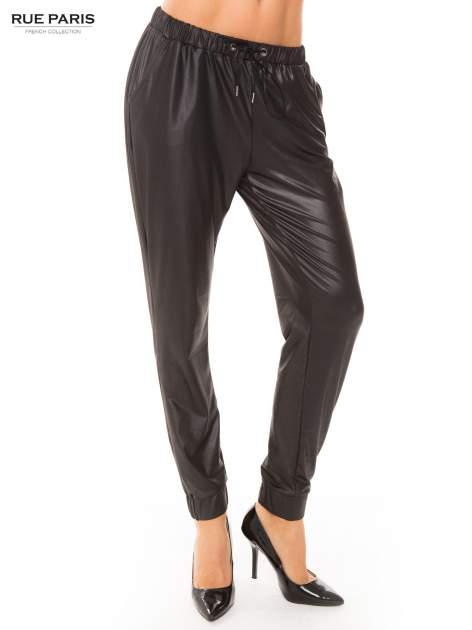 Czarne spodnie dresowe ze zwężanymi nogawkami z efektem połysku                                  zdj.                                  1