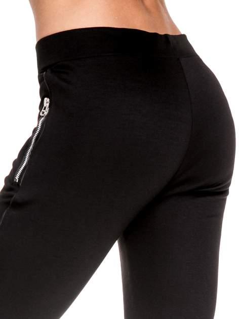 Czarne spodnie materiałowe tregginsy ze skórzanym lampasem i zamkami                                  zdj.                                  7