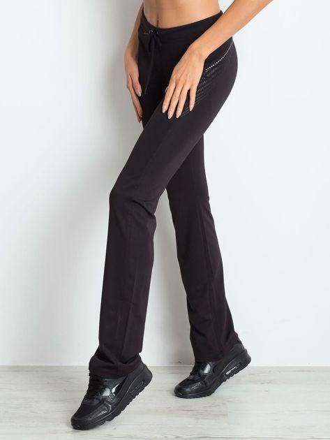 Czarne spodnie z troczkami i wzorkiem po boku                              zdj.                              3