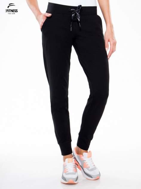 Czarne wąskie spodnie dresowe wiązane w pasie na wstążkę                                  zdj.                                  1