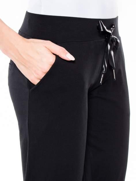 Czarne wąskie spodnie dresowe wiązane w pasie na wstążkę                                  zdj.                                  6