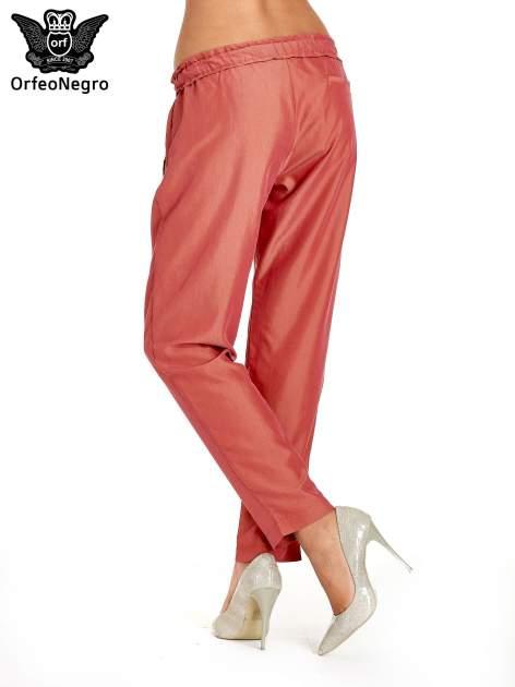 Czerwone lejące spodnie wiązane w pasie