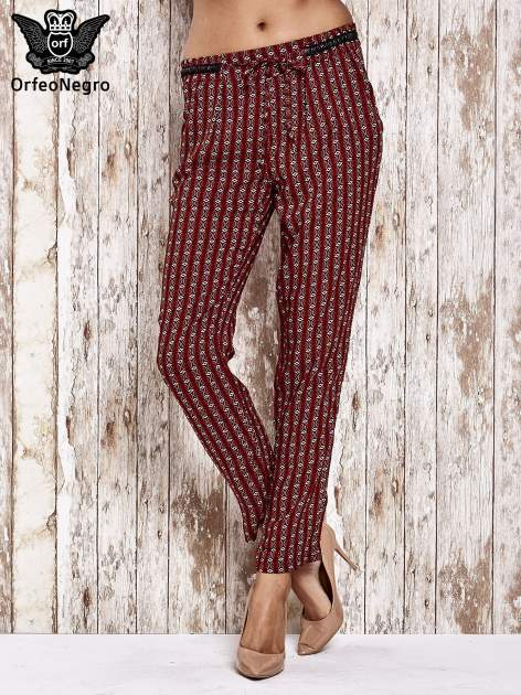 Czerwone lejące wzorzyste spodnie                                  zdj.                                  1