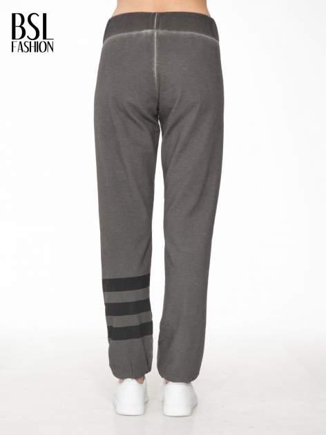 Grafitowe dresowe spodnie damskie z numerkiem i paskami na nogawkach                                  zdj.                                  4