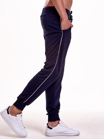 Granatowe dresowe spodnie męskie z lampasami po bokach i aplikacją                                  zdj.                                  4