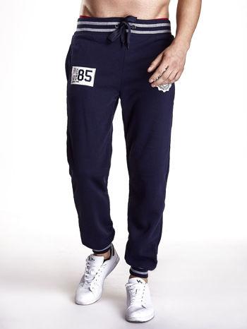 Granatowe dresowe spodnie męskie z naszywkami i kieszeniami                                  zdj.                                  1