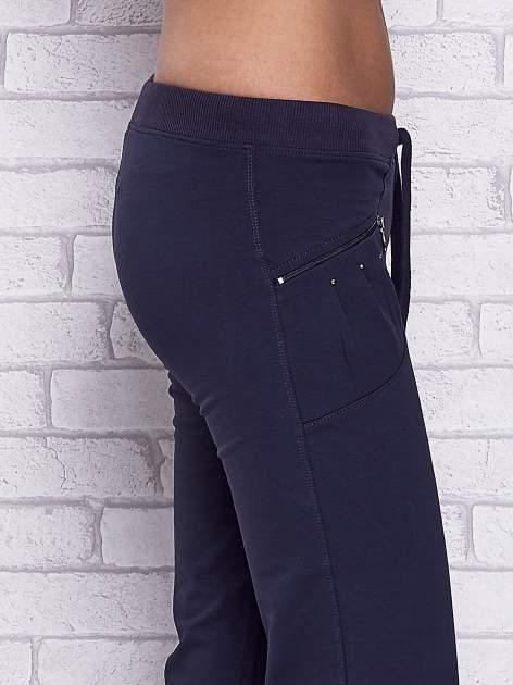 Granatowe spodnie capri z boczną kieszonką i dżetami                                  zdj.                                  5