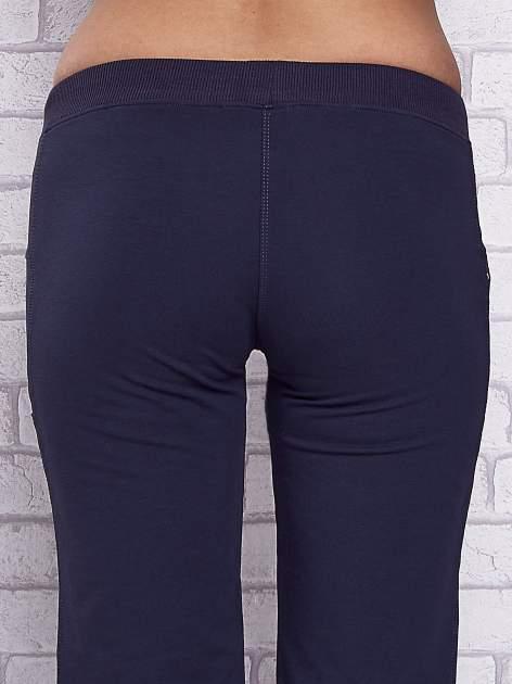 Granatowe spodnie capri z boczną kieszonką i dżetami                                  zdj.                                  6