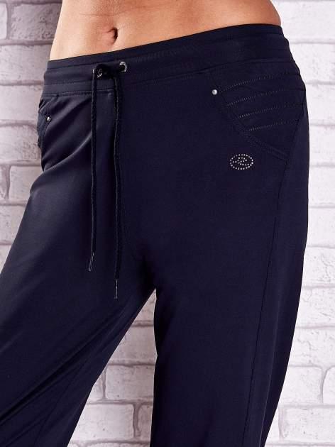 Granatowe spodnie capri z haftowanymi wstawkami PLUS SIZE                                  zdj.                                  4
