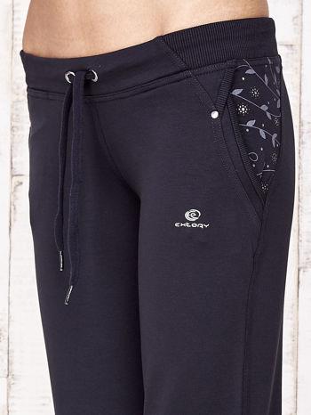 Granatowe spodnie dresowe capri z kwiatowymi kieszeniami                                  zdj.                                  6