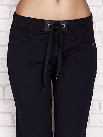 Granatowe spodnie dresowe capri z ozdobnym przeszyciem w pasie                                  zdj.                                  4