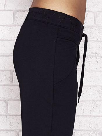 Granatowe spodnie dresowe capri z ozdobnym przeszyciem w pasie                                  zdj.                                  5