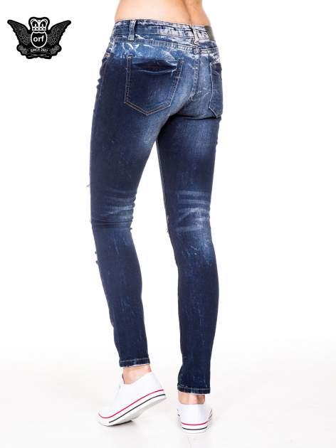 Granatowe spodnie jeansowe rurki z poszarpanymi nogawkami                                  zdj.                                  4