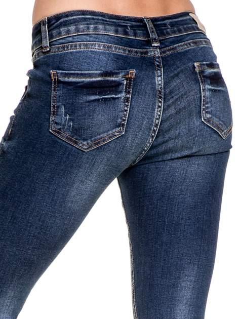 Granatowe spodnie skinny jeans z przecieraną nogawką z przodu                                  zdj.                                  8