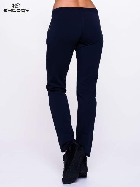 Jasnogranatowe spodnie dresowe z dżetami przy kieszeniach                                  zdj.                                  4