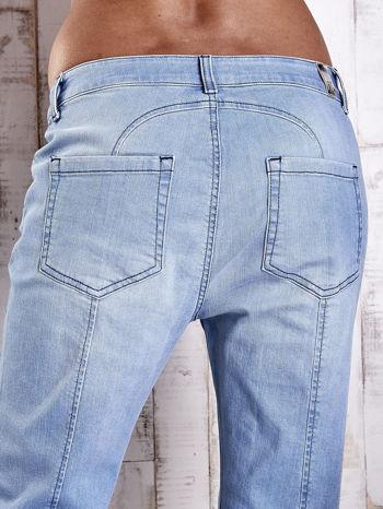 Jasnoniebieskie jeansowe spodnie z guzikami na nogawkach                                  zdj.                                  6