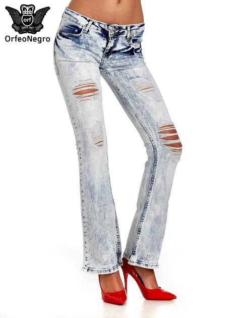 Jasnoniebieskie spodnie jeansowe dzwony z dziurą na kolanie                                  zdj.                                  1