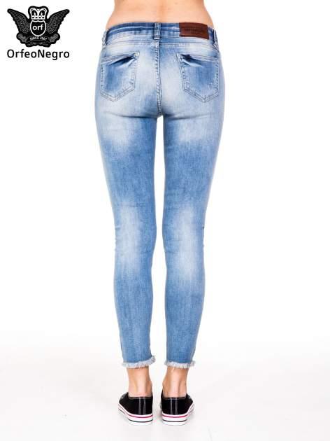 Jasnoniebieskie spodnie jeansowe rurki z poszarpaną nogawką na dole                                  zdj.                                  6
