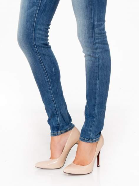 Jasnoniebieskie spodnie jeansowe rurki z przeszyciami na kieszeniach                                  zdj.                                  8
