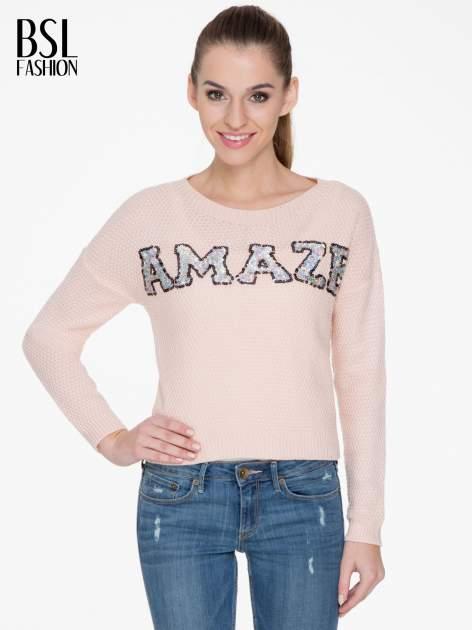 Jasnoróżowy sweter z napisem AMAZE z cekinów