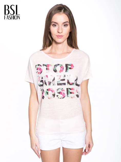 Jasnoróżowy t-shirt z kwiatowym napisem STOP SMELL ROSES