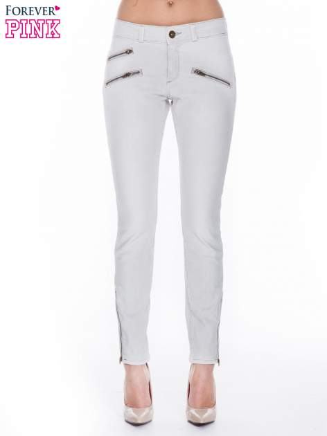 Jasnoszare spodnie jeansowe typu skinny z suwakami na górze i przy nogawkach