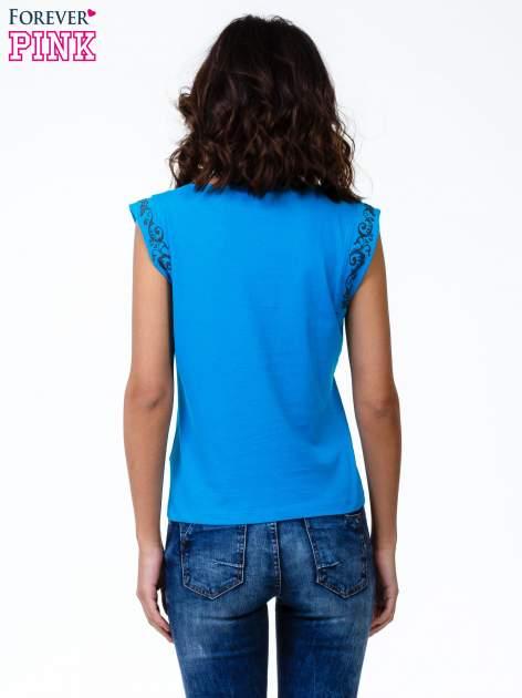 Niebieski t-shirt z ornamentem na rękawach                                  zdj.                                  4
