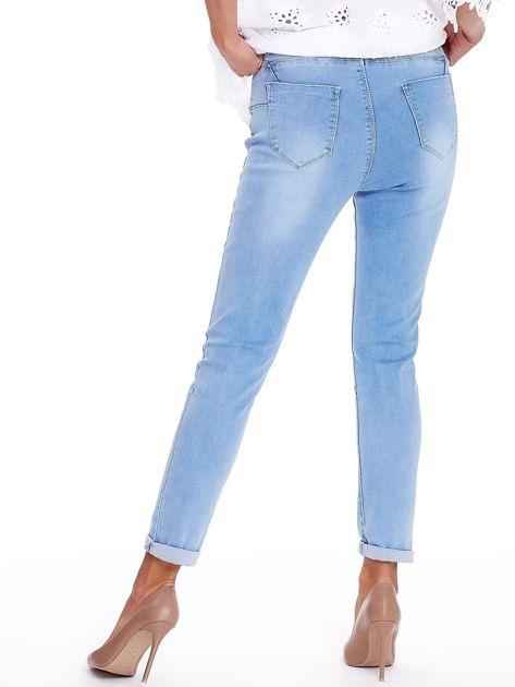 Niebieskie jeansy z przedarciami na kolanach                              zdj.                              2