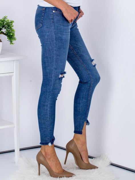 Niebieskie jeansy z rozdarciami i wystrzępionymi nogawkami                              zdj.                              3