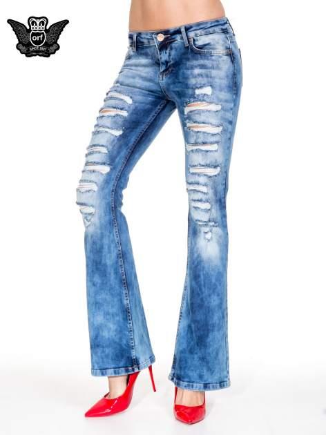 Niebieskie spodnie jeansowe dzwony z rozdarciami cut out                                  zdj.                                  1
