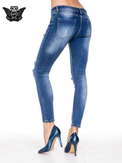 Niebieskie spodnie jeansowe rurki z dziurami i cieniowaniem                                  zdj.                                  4