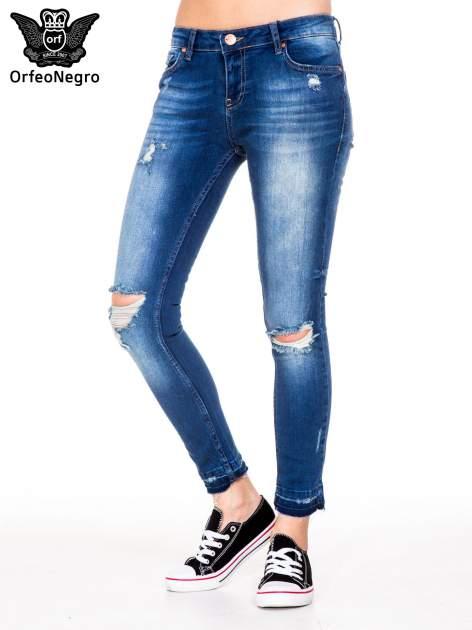 Niebieskie spodnie jeansowe rurki z dziurami i strzępioną nogawką