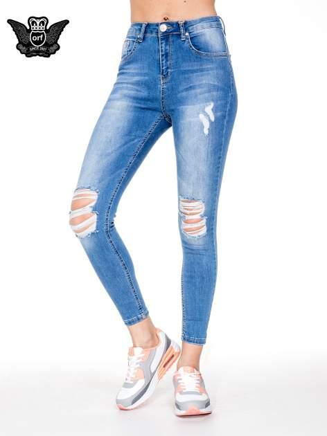 Niebieskie spodnie jeansowe rurki z wysokim stanem i dziurami na kolanach