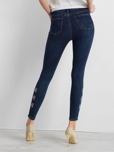 Niebieskie spodnie jeansowe z aplikacją na nogawkach                              zdj.                              2