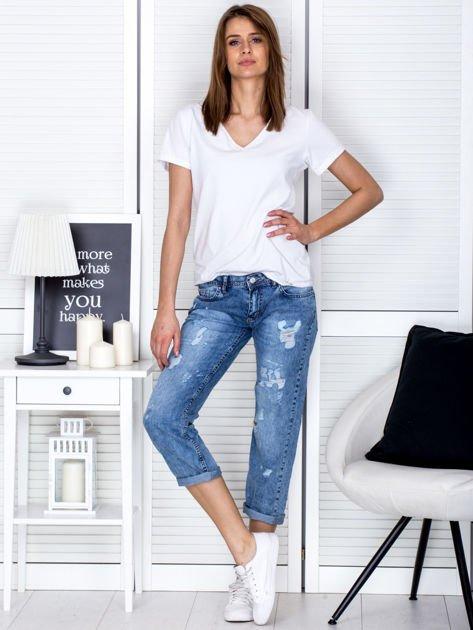 Niebieskie spodnie jeansowe z dekatyzacją i przedarciami                                  zdj.                                  4