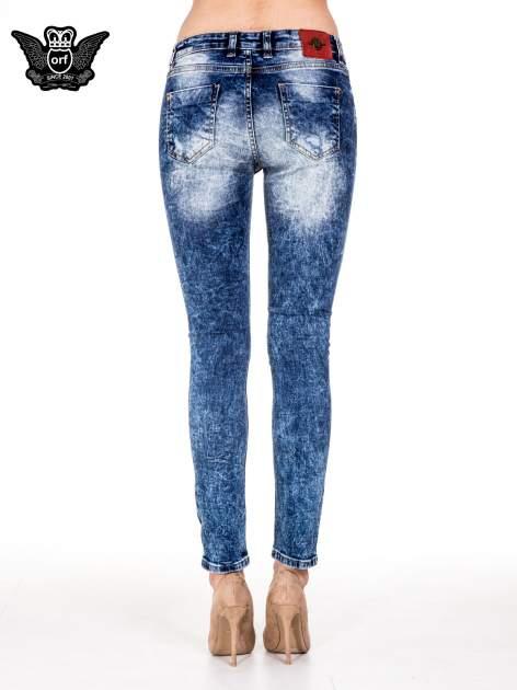 Niebieskie spodnie skinny jeans z rozdarciami i modelującym rozjaśnieniem                                  zdj.                                  4