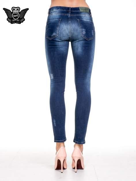 Niebieskie spodnie skinny jeans z rozdarciami na kolanach                                  zdj.                                  5