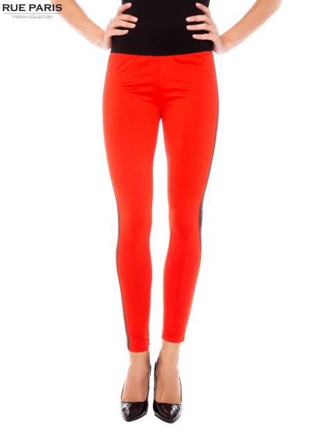Pomarańczowe legginsy ze skórzanymi lampasami po bokach